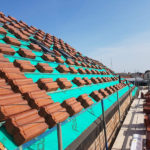 rows of stacked roof tiles on roof prepared to be installed tiling