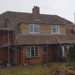 house with scaffolding on exterior for roofing repairs